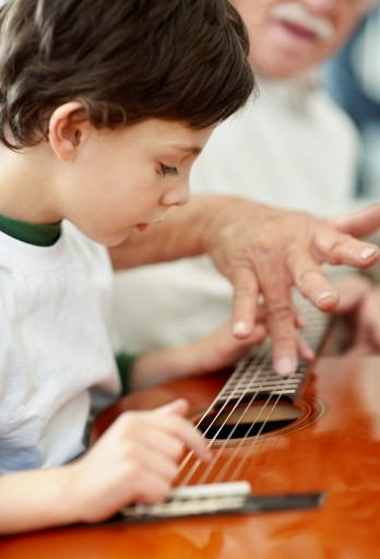 Side view of little boy playing the guitar with help from his grandfather
