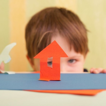 Small boy and little house made with color paper and scissors