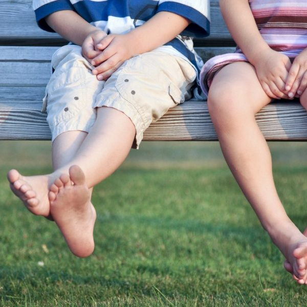 legs of barefoot boy and girl sitting on bench